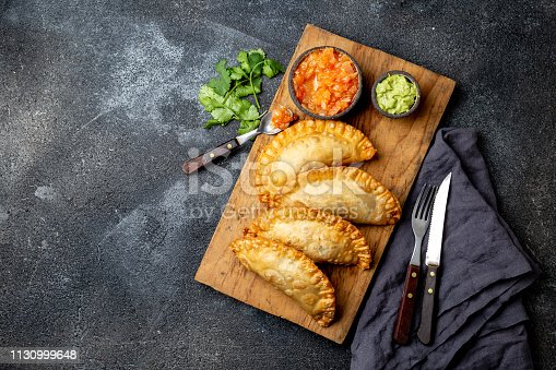 istock Latin American fried empanadas with tomato and avocado sauces. Top view 1130999648