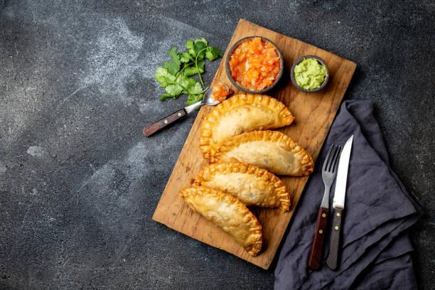empanadas fritadas latino-americanas com molhos do tomate e do abacate. vista superior - pastel de feira - fotografias e filmes do acervo