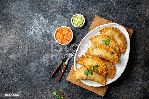 istock Latin American fried empanadas with tomato and avocado sauces. Top view 1130999661