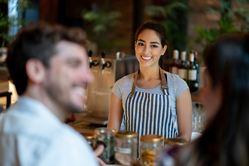 Latin american friendly waitress serving custmer couple on bar counter smiling very happy