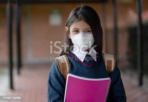Portrait of a Latin American girl looking happy at the school wearing a facemask during the COVID-19 pandemic - education concepts