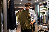 istock Latin american guy trying out a sweater on top at a men's clothing store 1197952617