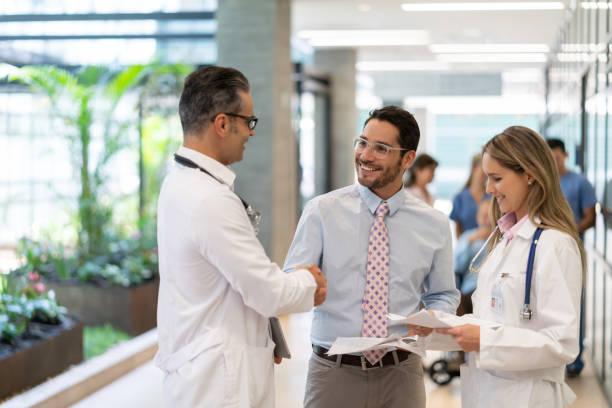 lateinamerikanische krankenhausaufsicht handschütteln mit männlichen arzt im krankenhaus, während einige dokumente - leitende position stock-fotos und bilder