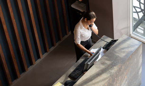 Latin american hotel receptionist taking a phonecall Latin american hotel receptionist taking a phonecall writing something down on document concierge stock pictures, royalty-free photos & images
