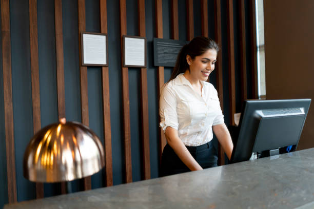 latin american hotel receptionist working behind counter smiling while looking at computer screen - hotel checkin foto e immagini stock
