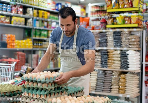 Latin american male business owner of a small market arranging the egg display - Small business concepts