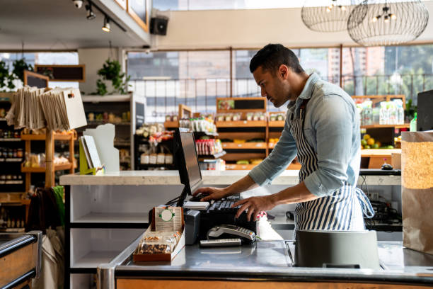Latin american male cashier at the supermarket looking something on system looking serious Handsome latin american male cashier at the supermarket looking something on system looking serious cash register stock pictures, royalty-free photos & images