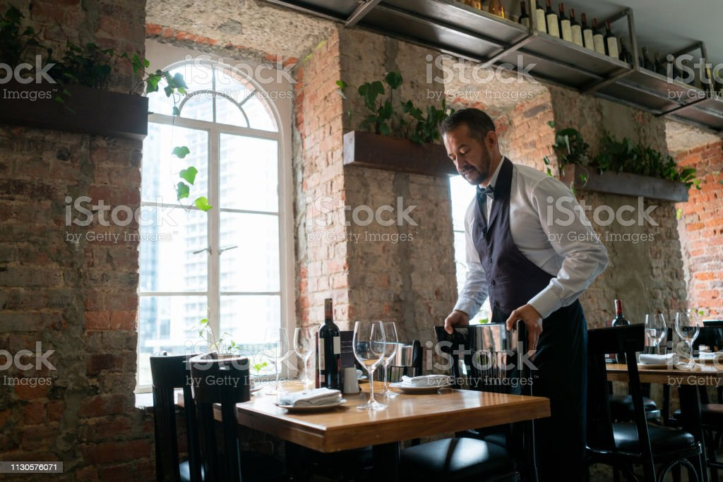 Latin american male waiter arranging chairs at a restaurant -...