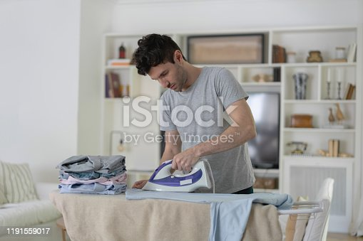 Latin american man at home ironing his button down shirts - Domestic lifestyles