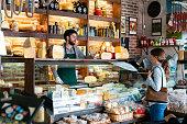 Latin american man working at a delicatessen suggeting a type of cheese to female customer - Small business concepts