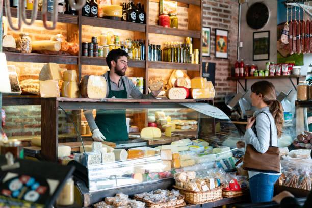 여성 고객에게 치즈의 종류를 suggeting 델리카트슨에서 일하는 라틴 아메리카 남자 - 시장 소매점 뉴스 사진 이미지