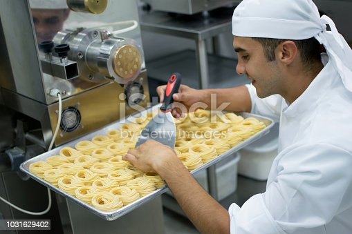 Latin american man working at a pasta factory and organizing a fresh batch of spaghetti on a tray looking very happy