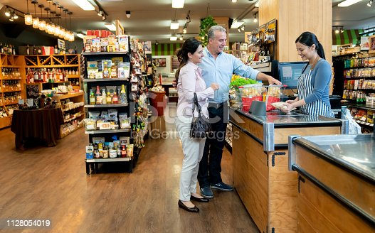 istock Latin american mature couple checking out at grocery store and friendly cashier scanning products 1128054019