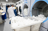 Latin american men working together loading a washing machine at a laundry service - Business industry concepts
