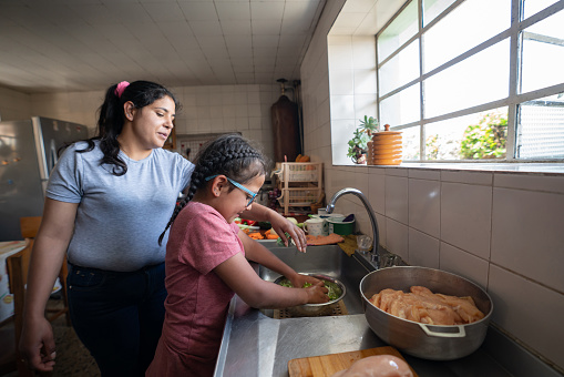 Latin American mother teaching her daughter to cook dinner at home - lifestyle concepts