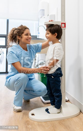 istock Latin american nurse measuring a pediatrics patient checking hos growth progress both smiling 1141832676