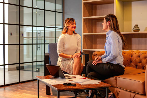 Lateinamerikanische Bürokollegen, zwei attraktive Damen, sind dabei, eine Geschäftsdiskussion in der Office Lounge zu beenden; Datendiagramme und Laptop-Computer auf dem Couchtisch wurden verwendet, um die Diskussion zu unterstützen. – Foto