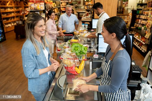 istock Latin american people at a grocery store doing checkout with friendly cashiers all smiling 1128048573