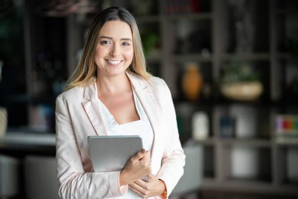 latijns-amerikaanse onroerende goederenagent houden van een tablet en kijken camera glimlachen - verkoopster stockfoto's en -beelden