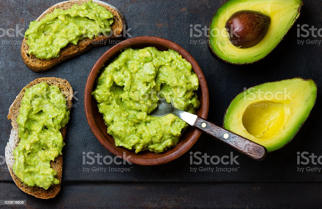 Latin American sauce guacamole and avocado sandwiches on dark background. stock photo