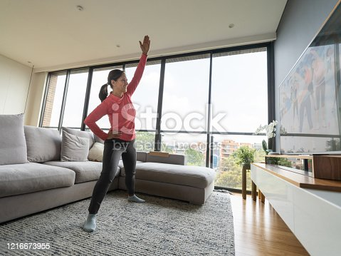Latin american senior woman following an aerobics class online looking at TV screen while on lockdown - Stay at home, keep safe. **IMAGE ON SCREEN BELONGS TO US**