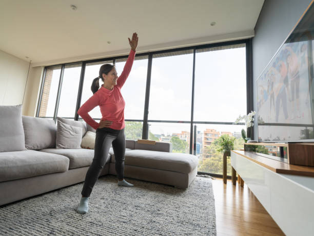 latin american senior woman following an aerobics class online looking at tv screen while on lockdown - exercise at home stock pictures, royalty-free photos & images
