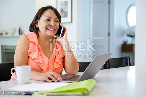 Hispanic senior woman using laptop at dining table and smiling as she hears good news on smart phone.