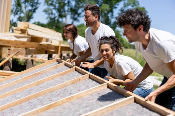 volontari latinoamericani che lavorano sodo in un progetto di costruzione di beneficenza - costruire foto e immagini stock