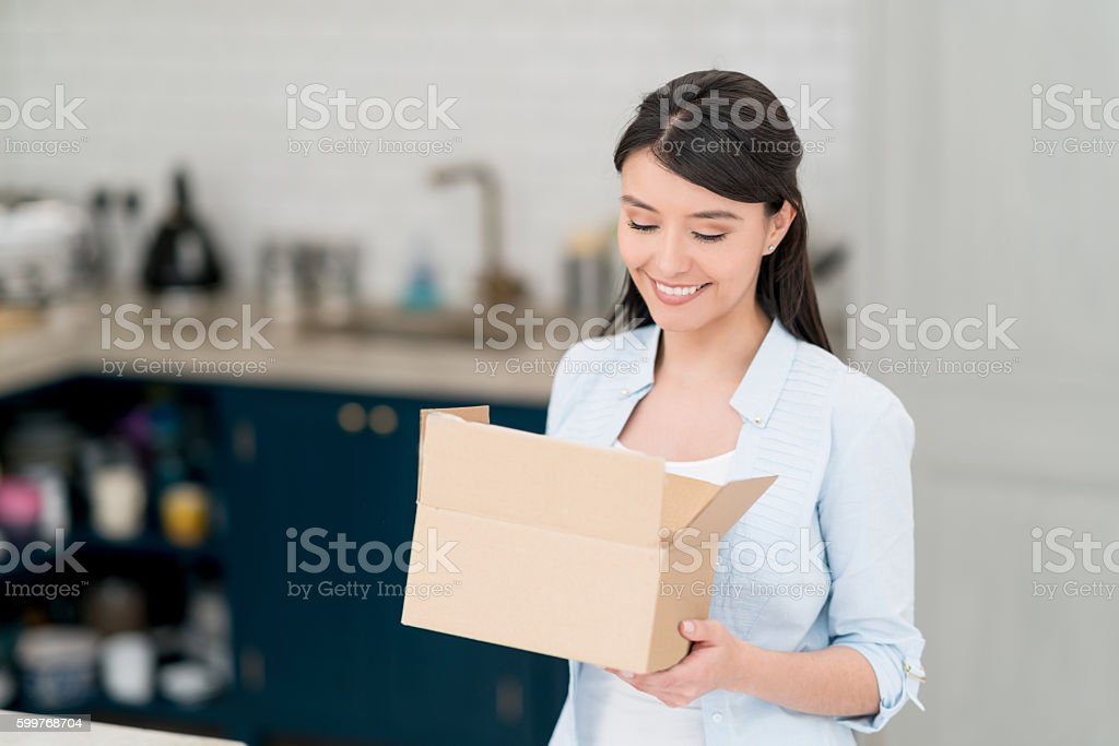 Latin American woman getting a parcel in the mail stock photo