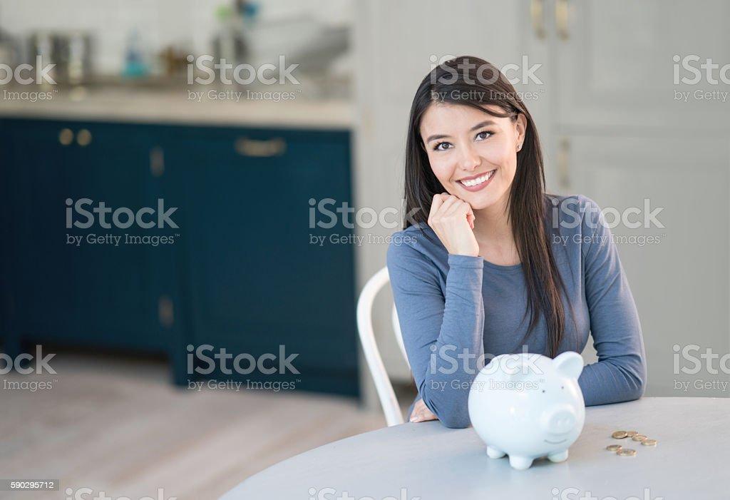 Latin American woman saving in a piggybank royaltyfri bildbanksbilder