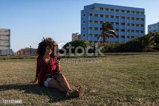 946192604 istock photo Latin American woman surfing the net on smart phone 1211325892