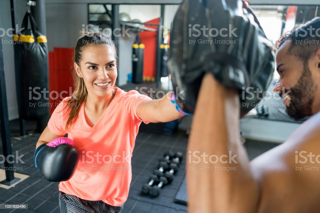Latin american woman training kickboxing with her male coach stock photo