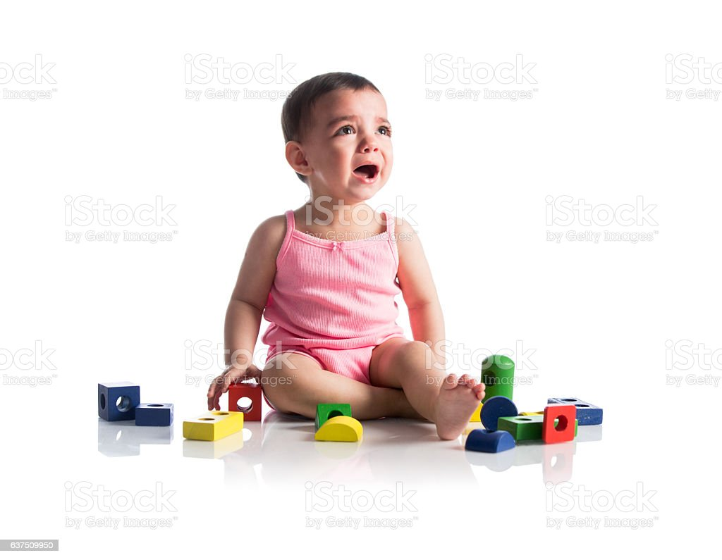 Latin baby girl sitting with toys and crying - foto de stock