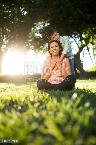 811227514 istock photo Latin boy embracing mother from behind and smiling 807897880