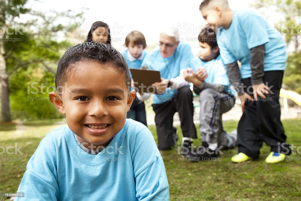 Latin boy foreground, background is children's sports team with coach. royalty-free stock photo
