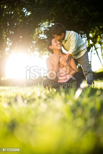 811227514 istock photo Latin boy kissing mother on forehead 811220348