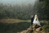 A latin mid adult bride and mature groom standing on rocks next to a lake, holding hands and smiling at each other in a horizontal full length shot outdoors.