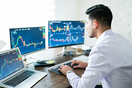 Hispanic young male stock trader typing on keyboard while using computer at home