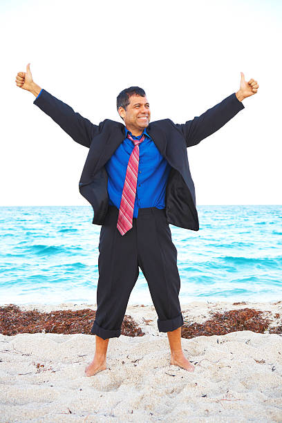 Latin business male enjoying success at the beach stock photo