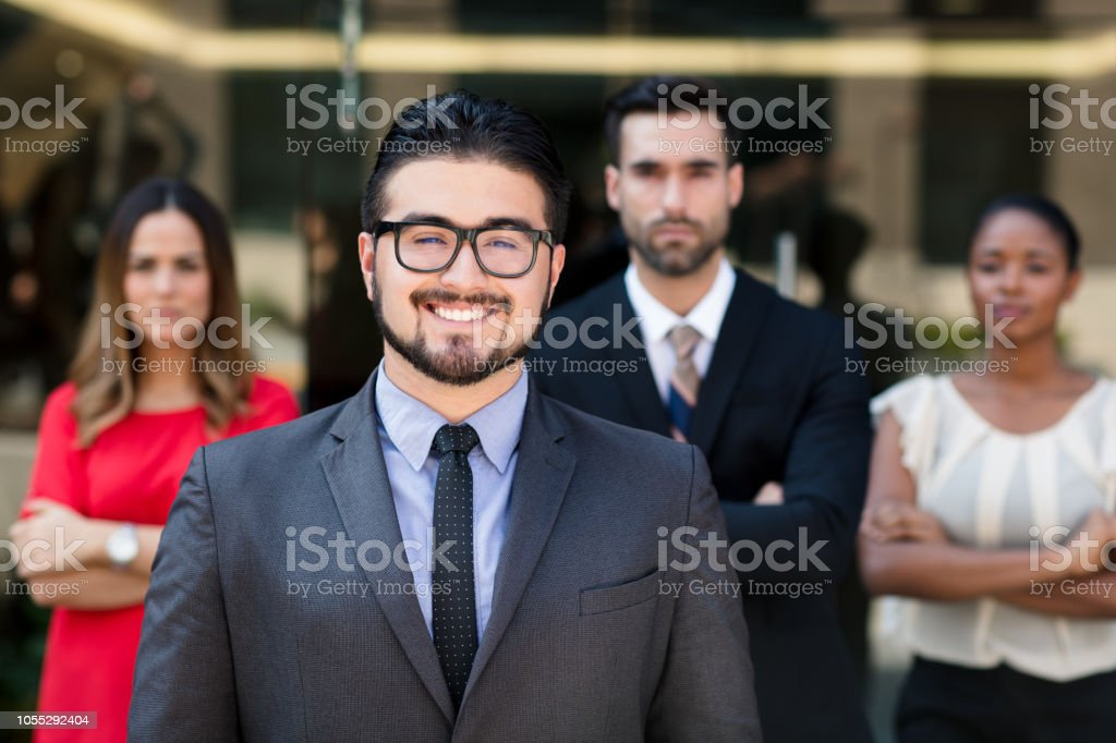 Latin business man posing with group in background stock photo