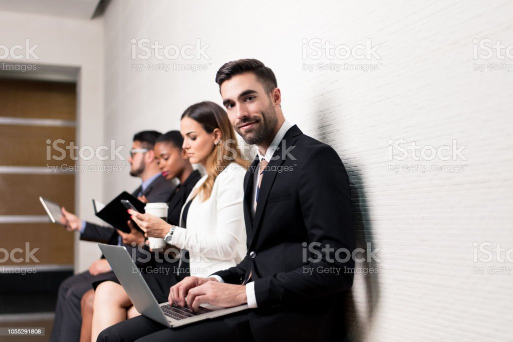 Latin business man sitting in waiting room with laptop stock photo