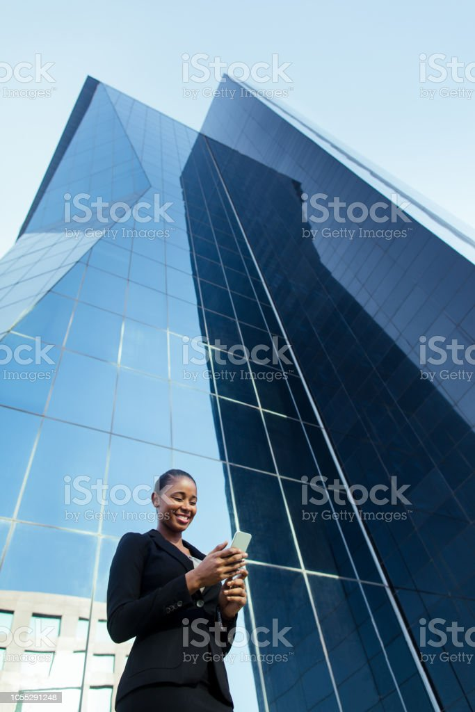 Latin business woman happily reading from phone outdoors stock photo