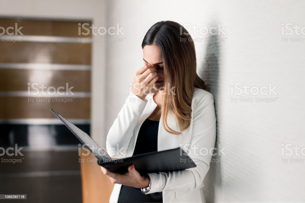 Latin business woman worried with portfolio in hand stock photo