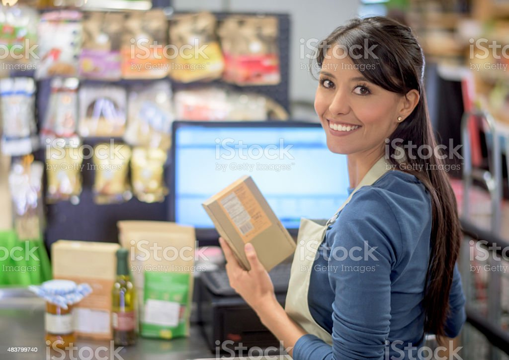 Latin cashier working at a supermarket stock photo