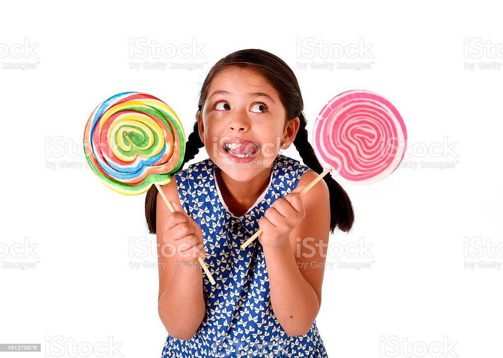 latin child holding two big lollipop  in sugar addiction concept stock photo