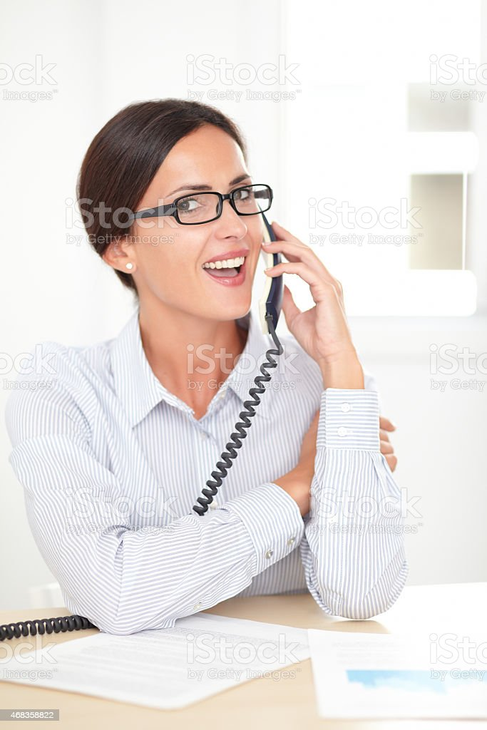 Latin company secretary conversing on the phone royalty-free stock photo
