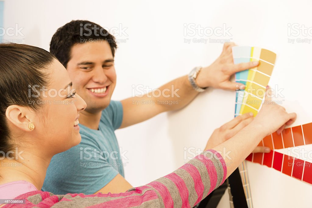 I like that one! Young Latin couple chooses paint colors for wall in...