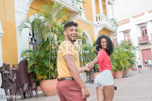 Latin couple made up of black curly-haired woman in brown skin, red blouse and jean short that holds her boyfriend Latin man with curly hair and yellow sweater who is also holding her hand as they walk along and behind her and they look at the camera with a big smile on their faces for the happiness of knowing Cartagena