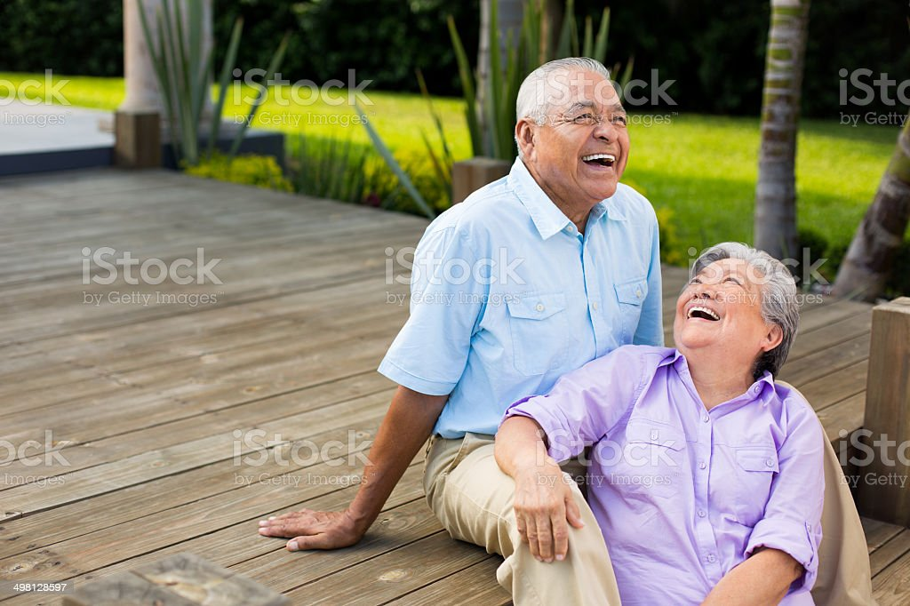 Latin couple laughing on deck stock photo
