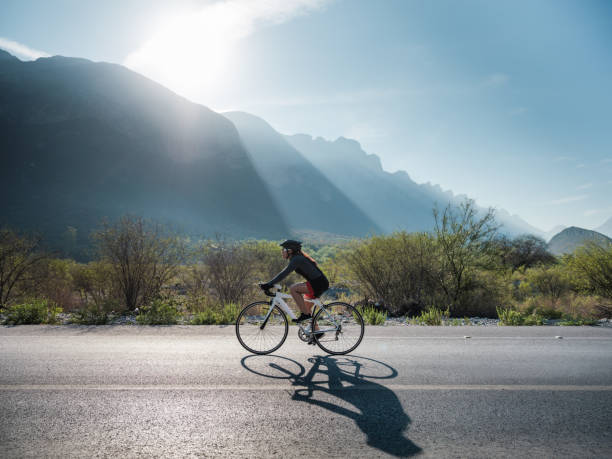 Latin cyclist on the road with bike stock photo